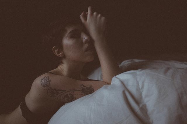 Žena v spodnej bielizni a výrazným tetovaním na ruke kľačí pri posteli