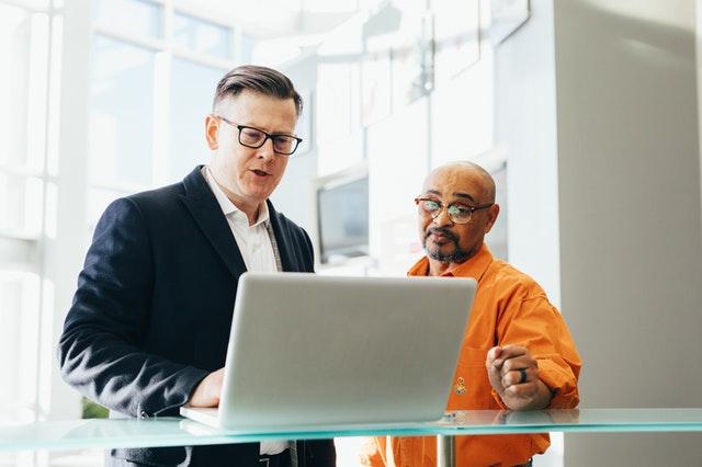 Dvaja muži, ktorí sa rozprávajú pri počítači.jpg