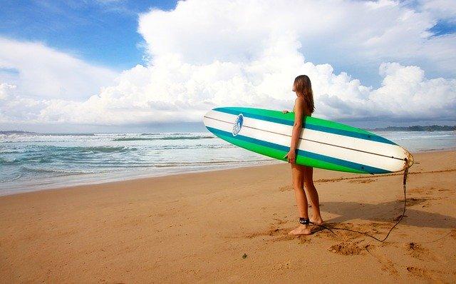 Žena v plavkách a so surfom v ruke stojí na pláži a pozerá na more.jpg