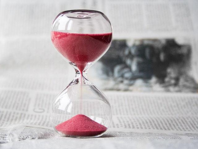 Sklenené presýpacie hodiny s červeným pieskom, položené na novinách.jpg